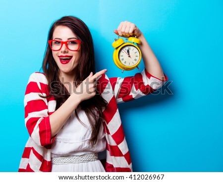 portrait of the beautiful young woman with yellow clock on the blue background - stock photo