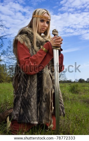 Portrait of the blonde girl in the Scandinavian suit with sword - stock photo
