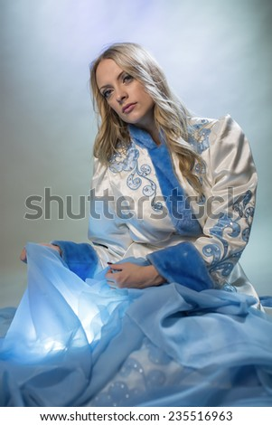 Portrait of the blonde with a blue fabric - stock photo