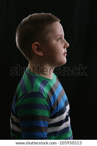 Portrait of the boy in profile on black background - stock photo