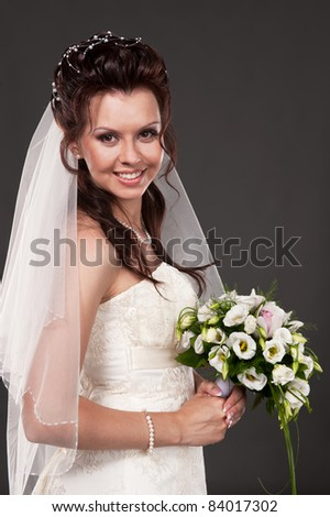 Portrait of the bride in studio on a grey background - stock photo