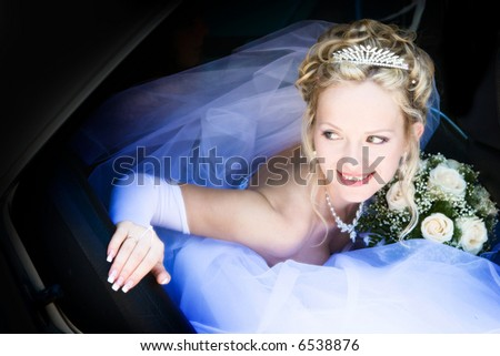 Portrait of the bride sitting in the car - stock photo