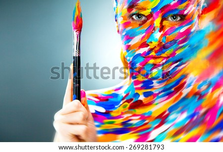 Portrait of the bright beautiful emotional woman with art make-up and brush in her hand - stock photo
