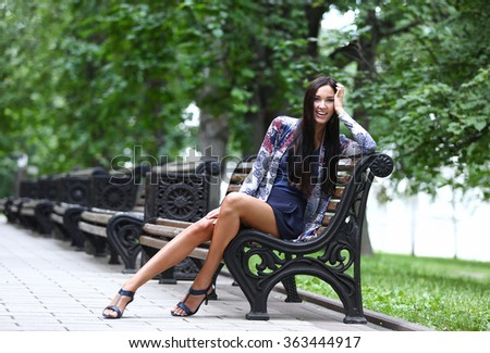 Portrait of the brunette with long hair sitting on a park bench - stock photo