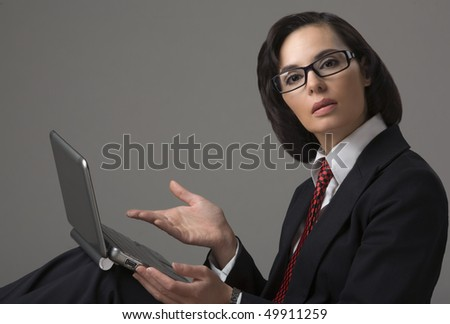 Portrait of the business woman on a grey background with the laptop - stock photo