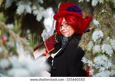 Portrait of the cosplay girl with chainsaw in the fir-tree - stock photo