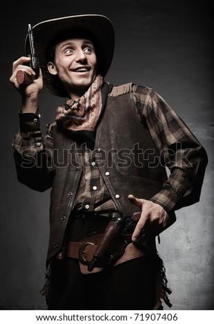 Portrait of the cowboy closeup. The smiling cowboy with pistols closeup - stock photo
