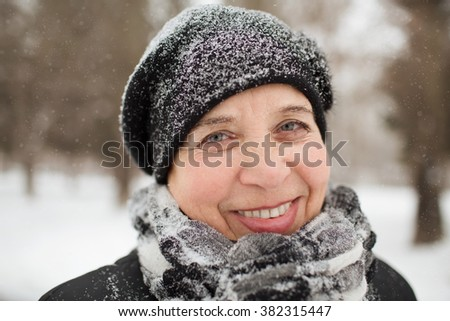 portrait of the elderly woman on walk in winter park - stock photo