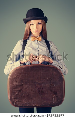 Portrait of the elegant girl model in bowler hat holding her old suitcase. Refined style of old Europe.  - stock photo
