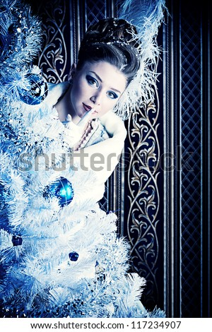 Portrait of the elegant woman posing with Christmas tree over vintage background. - stock photo
