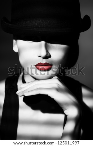 Portrait of the elegant young woman posing in black pot hat. Light and shadow. - stock photo