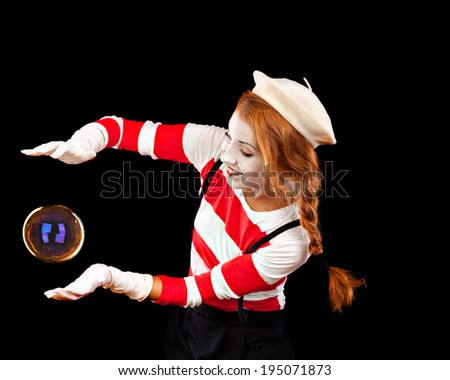 Portrait of the female MIM comedian catches bubbles, isolated on black background - stock photo