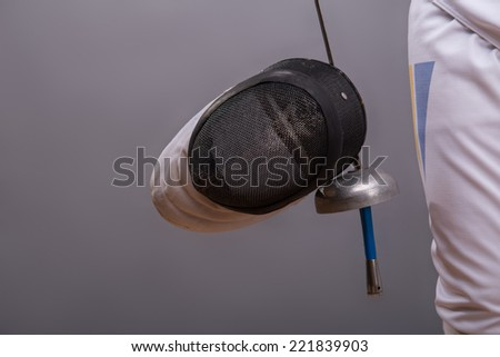 Portrait of the fencing mask which is hanging on the rapier in the hands of the fencer - stock photo