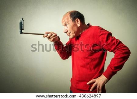 portrait of the funny senior man taking selfie - stock photo