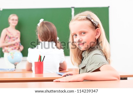 portrait of the girl in the class, the teacher tells the next school board - stock photo
