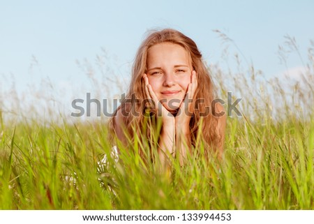 Portrait of the girl lying in a green grass - stock photo