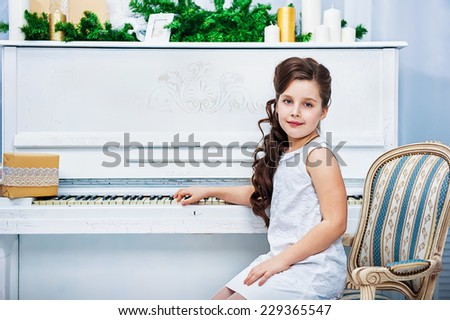 Portrait of the girl near white piano - stock photo