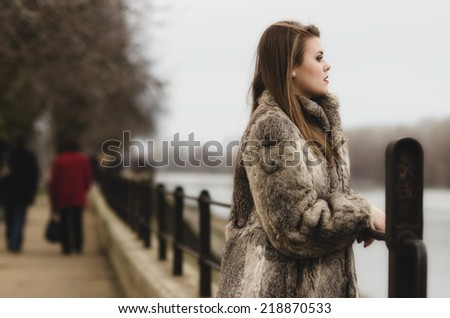 Portrait of the glamorous brunette lady in expensive fur coat watching river. - stock photo