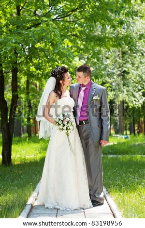 Portrait of the groom and the bride in park in the summer sunny day - stock photo