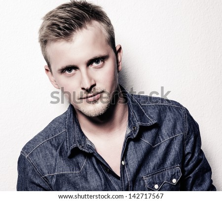 portrait of the handsome young man in jeans clothes on a white background - stock photo