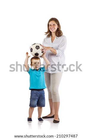 Portrait of the happy pregnant mother with her son playing with soccer ball - stock photo