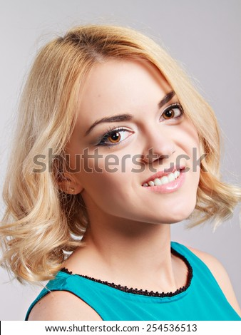 Portrait of the happy smiling girl posing in studio on grey background. - stock photo