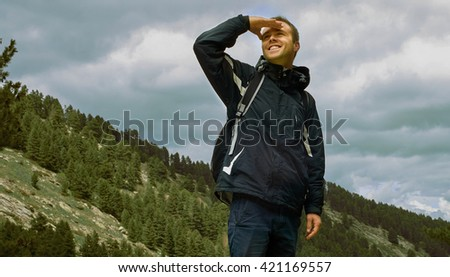 Portrait of the healthy smiling happy young man with backpack standing at the top of the hill with green forest in the background while hiking and looking forward -  Hard way to Success concept - stock photo