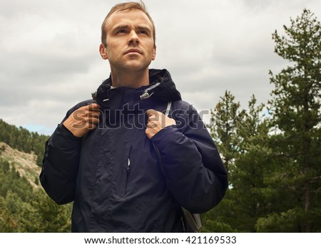 Portrait of the healthy young man with backpack standing at the top of the hill with green forest in the background while hiking and looking forward -  Hard way to Success concept - stock photo
