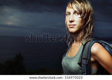 Portrait of the lady with backpack and wet clothes and hair - stock photo