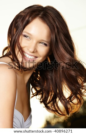 Portrait of the laughing curly beautiful woman in sunlight beams - stock photo
