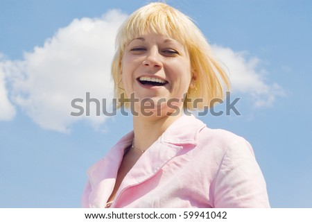 Portrait of the laughing girl against the sky - stock photo