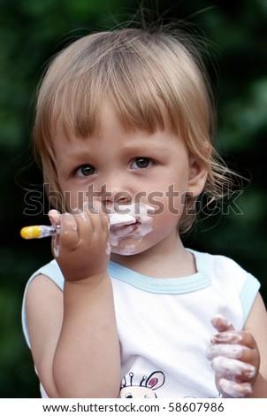 Portrait of the little boy eating yogurt - stock photo