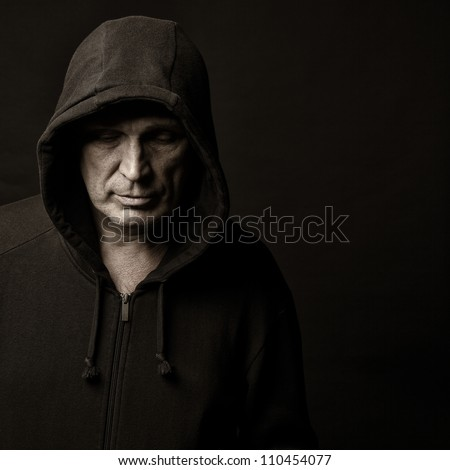 Portrait of the man in a hood against a dark background - stock photo