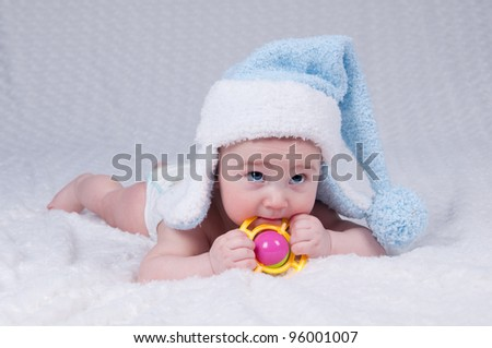 Portrait of the newborn close-up, a child in a blue, soft wool hat on a white background. - stock photo