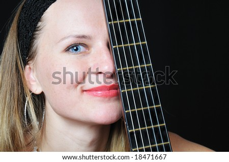 portrait of the nice woman behind fretboard - stock photo