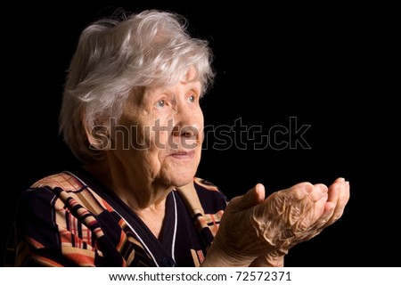 Portrait of the old woman a black background - stock photo