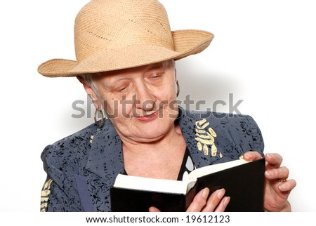 Portrait of the old woman in a hat with the book on a light background - stock photo