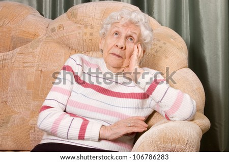 Portrait of the old woman on sofa - stock photo