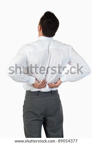 Portrait of the painful back of a young businessman against a white background - stock photo