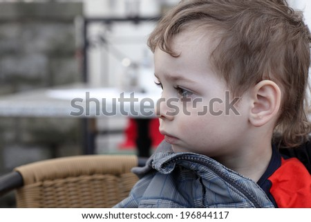 Portrait of the pensive boy in profile indoor - stock photo