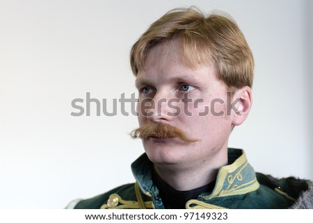 Portrait of the serious hussar on the wall background - stock photo