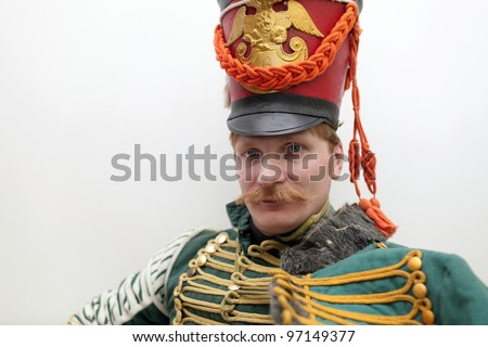 Portrait of the serious russian hussar on the wall background - stock photo