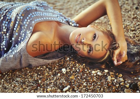 Portrait of the sexy woman on sea pebbles - stock photo