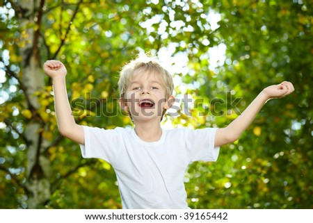 Portrait of the small laughing boy against park - stock photo