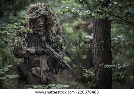 portrait of the soldier wearing ghille suit, holding assault rifle in forest. - stock photo