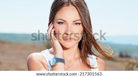 Portrait of the young beautiful smiling woman outdoors enjoying summer sun.  - stock photo