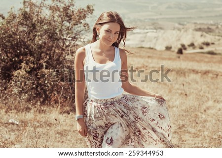 Portrait of the young beautiful smiling woman outdoors enjoying summer sun. wind in hair. girl in a long skirt and with long hair poses in warm spring day - stock photo