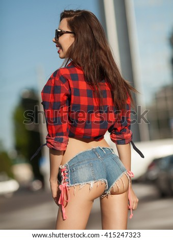 Portrait of the young beautiful smiling woman outdoors enjoying summer sun. Young woman outdoors portrait. Woman in jeans shorts and red shirt. Sexy woman buttocks. - stock photo