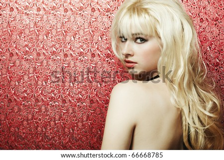 Portrait of the young blonde woman on a red background - stock photo