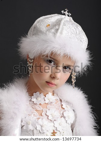 Portrait of the young girl in a fantastic winter suit on a dark background - stock photo
